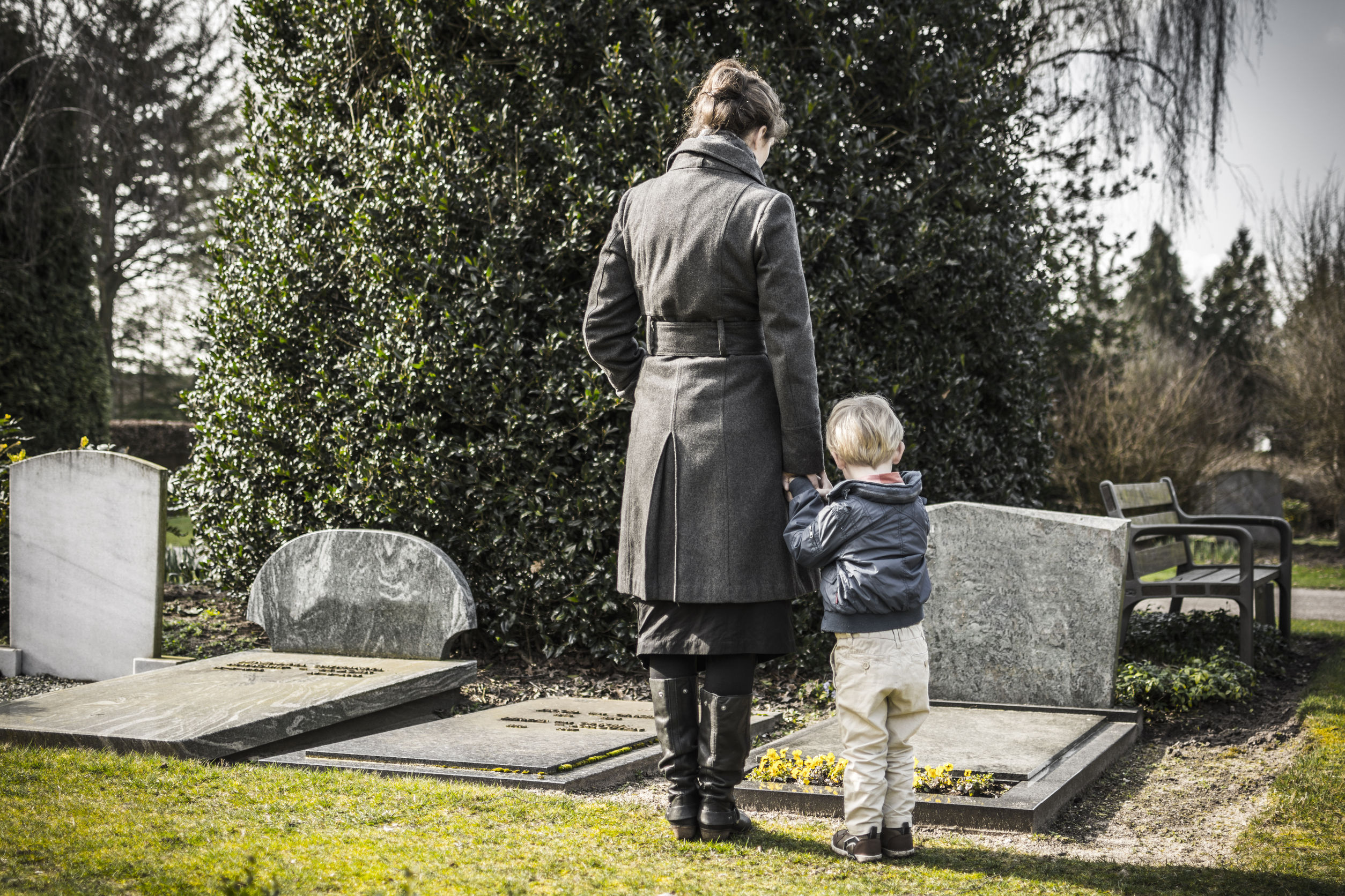 26592865 – woman and child looking at gravestone on graveyard